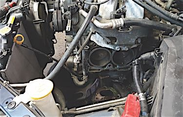 With a jack stand under the motor mount bracket, slowly lower the car to raise one side of the engine.